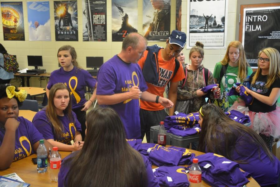 Yearbook adviser Alex Hollis hands out T-shirts made for yearbook staffer MeKayla Gist. Gist is battling osteosarcoma.