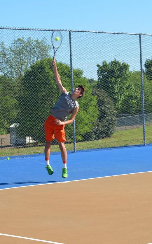 Junior Zack Martin smashes his first serve.