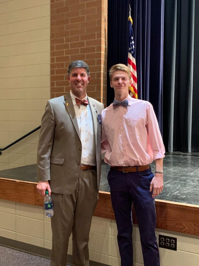 Chapman principal Andrew McMillan with senior Thomas Mathis. Mathis was recently named a state-level winner of the Heisman High School Scholarship.