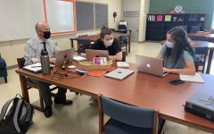 Yearbook adviser Alex Hollis works with new co-editors Ellie Mitchell (center) and Gabby Freire.